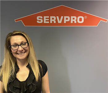 woman in black shirt smiling with a gray wall and orange SERVPRO logo behind her