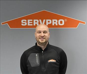 image of a smiling man standing under a SERVPRO logo