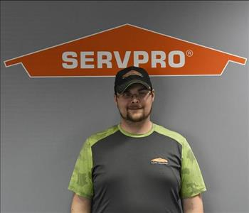 smiling man with beard and mustache under a SERVPRO logo