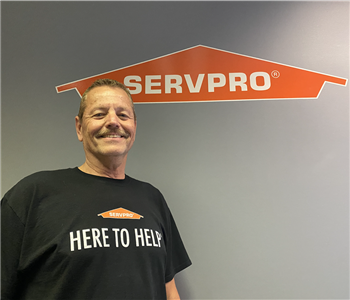 man smiling in a SERVPRO tee under a SERVPRO logo in front of a gray wall