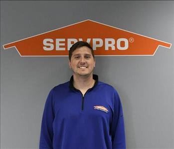 Image of a smiling man in a blue shirt standing under a servpro logo