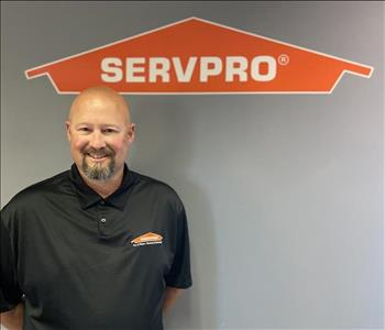 Man in black SERVPRO shirt smiling while under a SERVPRO logo