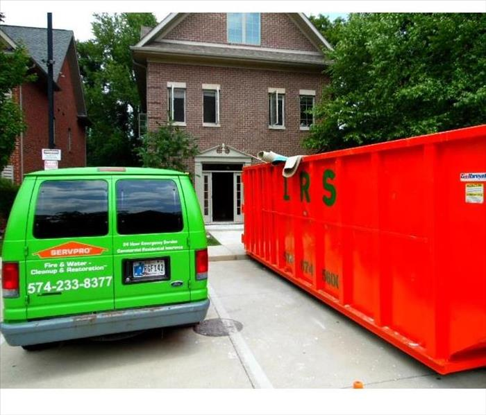 giant red dumpster with a green SERVPRO van next to it out in front of a home