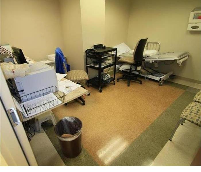 a healthcare room with gurney, printer and trashcan